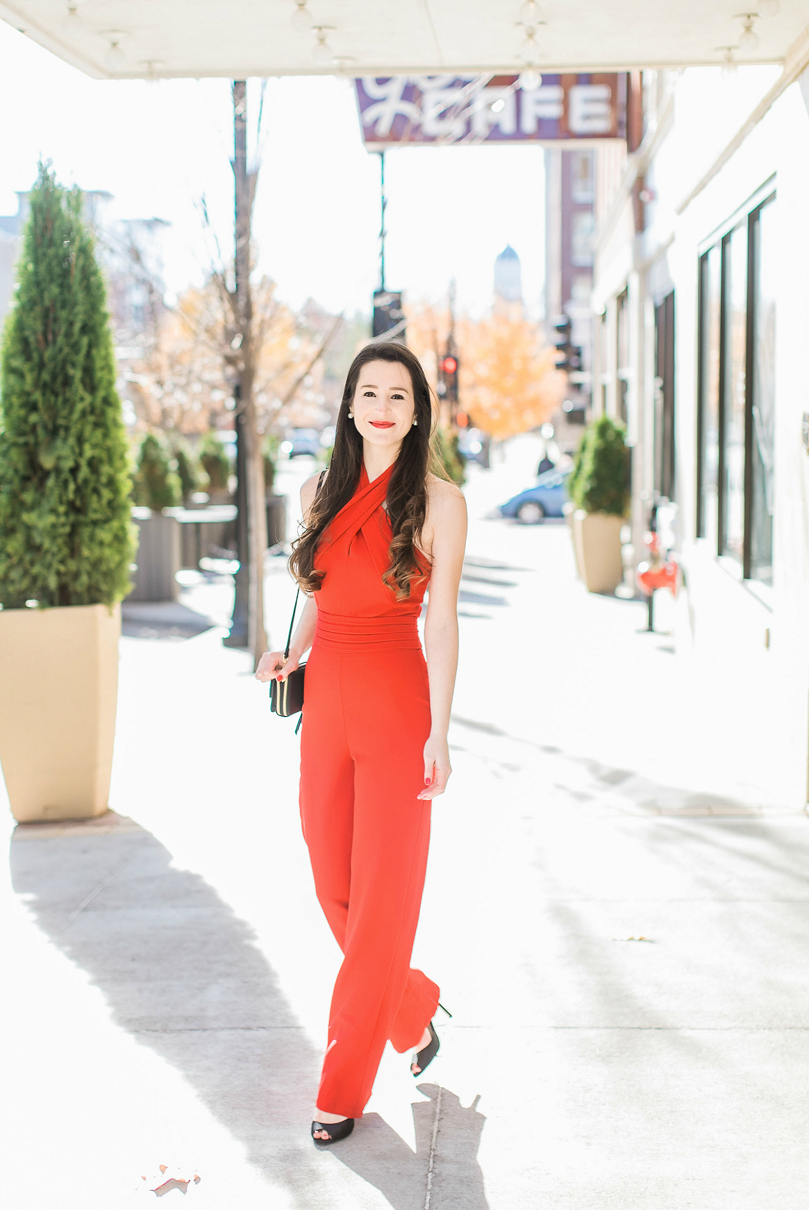 Bright red Adelyn Rae one piece jumpsuit styled with a black Vera Bradley RFID All-in-One Crossbody bag and Nina Shoes peep toe sandals by southern fashion blogger Stephanie Ziajka from Diary of a Debutante